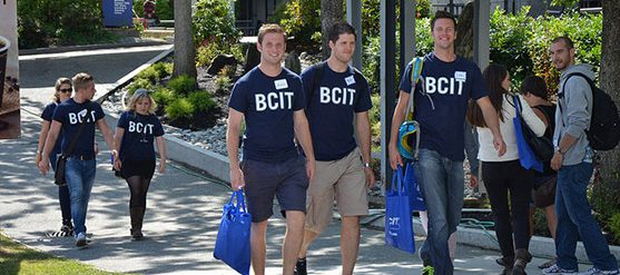 Photo of nine students walking, five of them are wearing navy blue t-shirts with BCIT in white lettering.