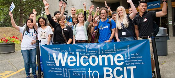 Students holding a welcome to bcit sign with white lettering in different languages on a blue background.