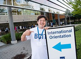 Student holding a sign saying international orientation in dark blue text and a light blue arrow underneath the text.