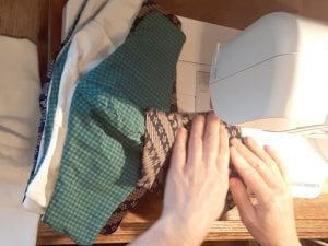 Hands on sewing machine with several face masks stacked beside