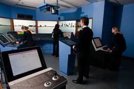 People at electronic simulator stations for marine purposes