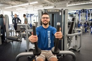 man sitting on excercise equipment wearing a BCIT recreation T-shirt and smiling