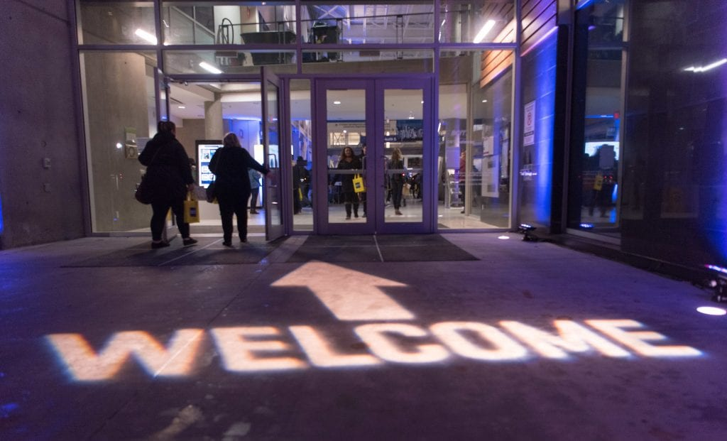 The word welcome and an arrow lighting the ground, pointing to the entrance of a BCIT building.