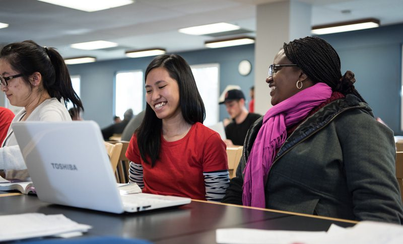 Female students smiling and looking at a laptop.