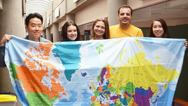 5 people holding a cloth world map.