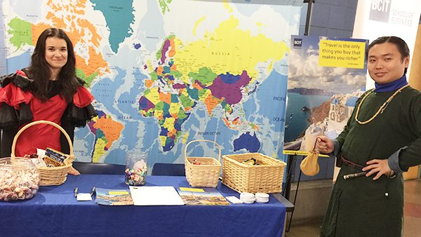 two people at a display booth with a world map behind them.