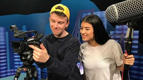 two youth working with a video camera smiling.