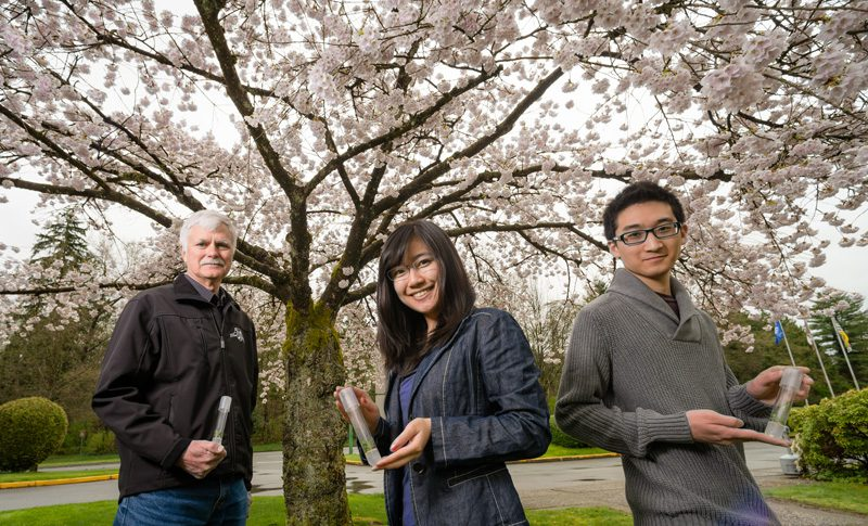 An older man, a woman and a younger man posing holding test tubs in front of a cherry tree.