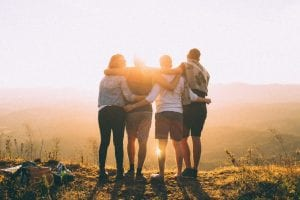4 friends standing with arms around each other looking at a sunset