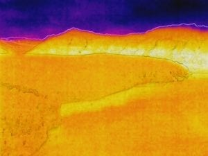 Thermal aerial image of glacier along waterway.