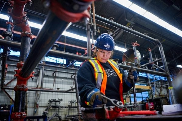 female with hard hat in piping shop
