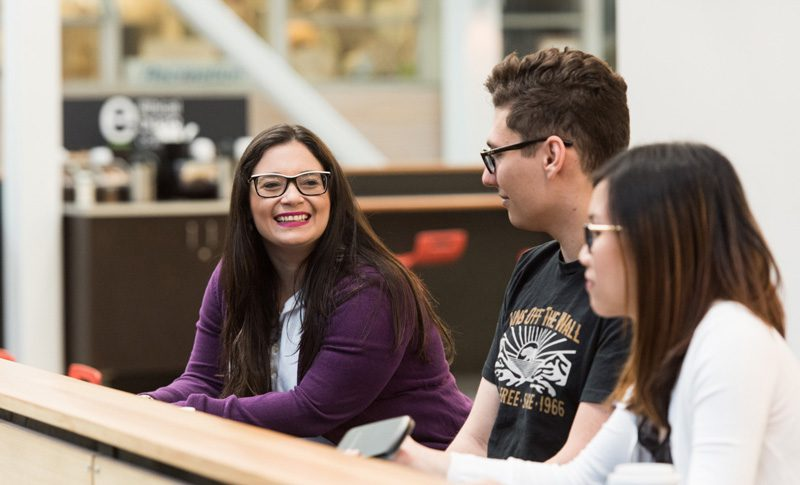 Three students sitting in the BCIT atrium, smiling.