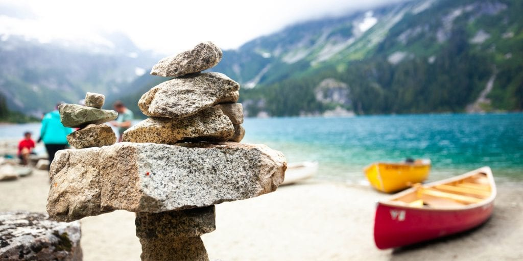Stacked rocks and a red canoe at the lakeside, Squamish.