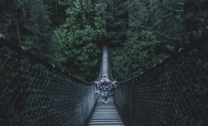 Person walking across Lynn Canyon bridge.