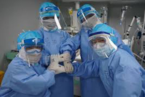 Nurses in full PPE including masks, face shields and gloves.