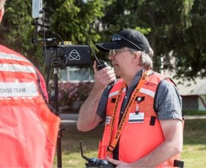 Man wearing safety vest, holding drone and talking on phone