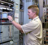 guy with blonde hair in beige t-shirt touching a mechanical panel