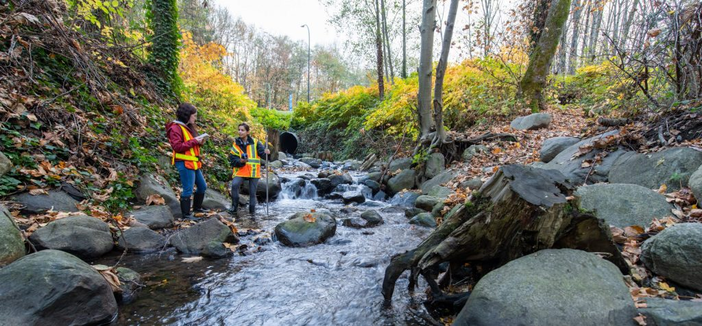two students in safety vest by the creek