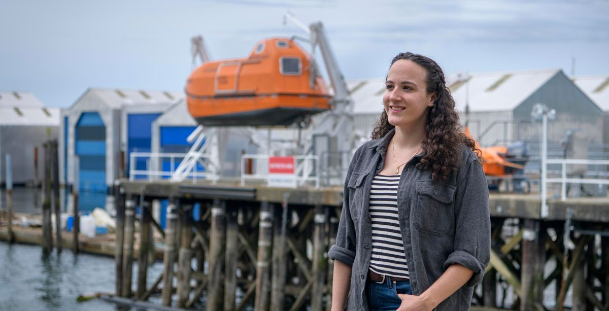 Woman standing at the harbour, with a lifeboat docked up high in the background.