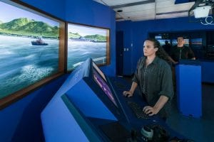 Indigenous female student stands in front of marine instrument training panel, watching the virtual screen.