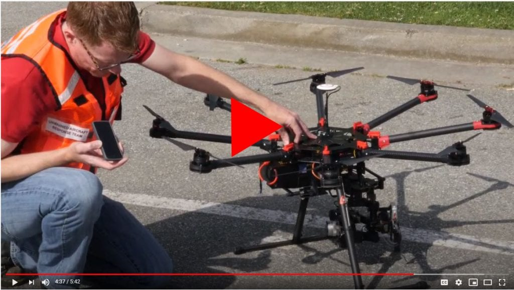 Man in safety vest setting up a drone