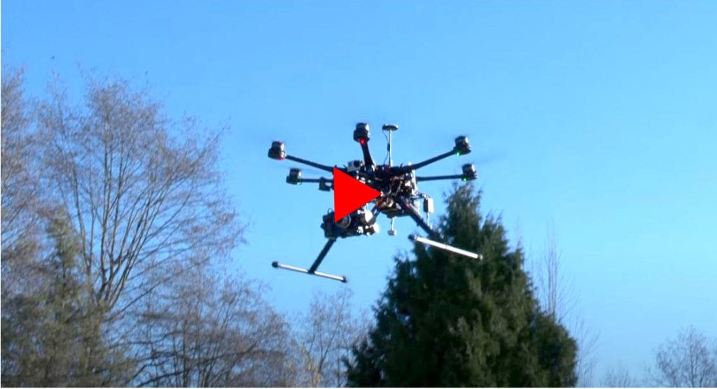 Hexacopter with camera mounted against blue sky