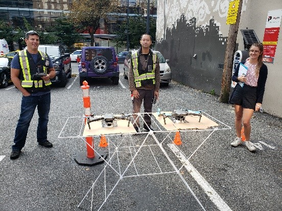 Two men and one woman standing behind a table with two drones