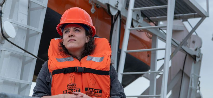 Women dressed as a deckhand in hard hat and life best standing in front of a lifeboat.