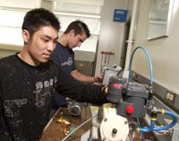 two male students in navy t-shirts look at some mechanical pieces