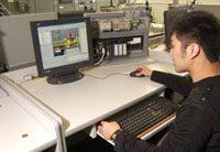 student of asian decent looks at a desktop computer