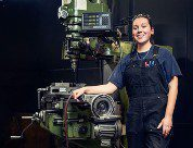 Chelsea Barron - female in blue overalls posing in front of a piece fo machinery