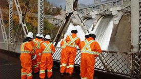 eight men in orange jumpsuits looking at a dam