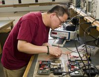 man in burgundy t-shirt with glasses looking at an electrical board