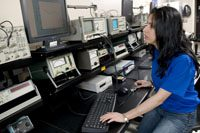 female with black hair and blue t-shirt looking at a computer-like device