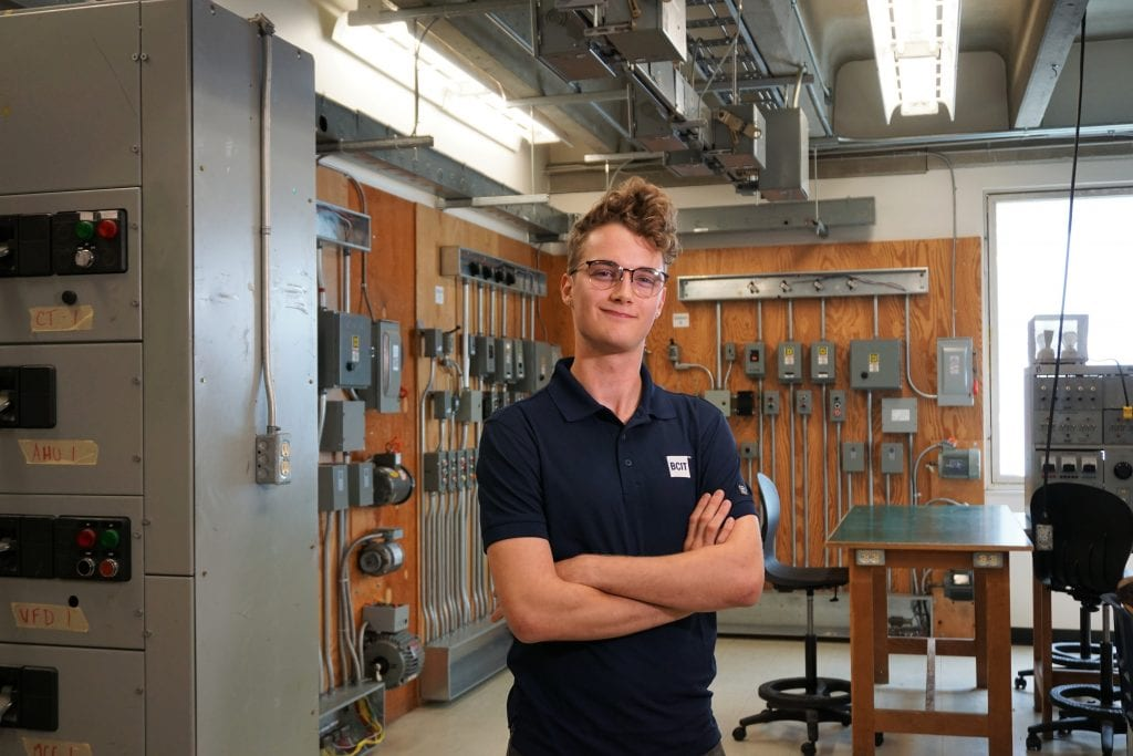 a male in BCIT polo shirt standing with arms crossed