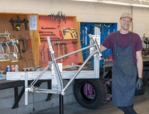 young guy with baseball cap and apron stood beside a bicycle frame