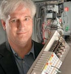 male with white hair holds piece of computer