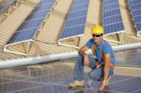 man kneeling down in sunglasses, blue jeans and yellow hardhat - solar panels in the background