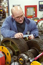 Millwright measuring a set of gears