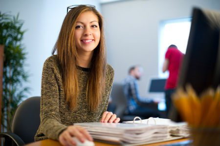 Young woman smiling with a folder open and holdng a mouse