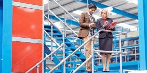 Image of business executives on staircase working with digital tablet - Businesspeople in factory