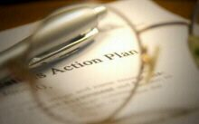 The text Action Plan behind a pair of glasses