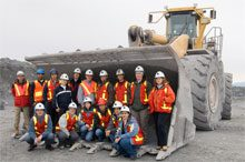 students in front of a mining vehicle