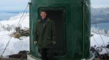 guy in green jacket outside of a green metal cylindrical structure