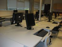 computer lab with three rows of black desktops on white, conjoined desks