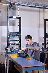 male working on some electronics on a blue desk