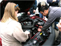 a woman and man look at a car engine