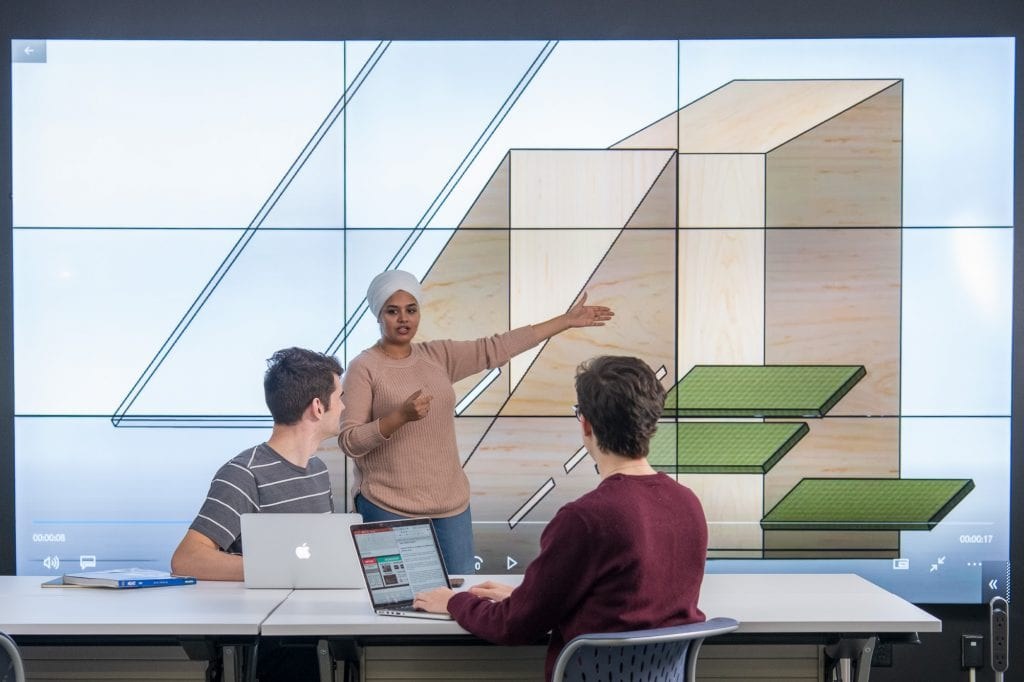 A student presents to two others in front of a large digital screen