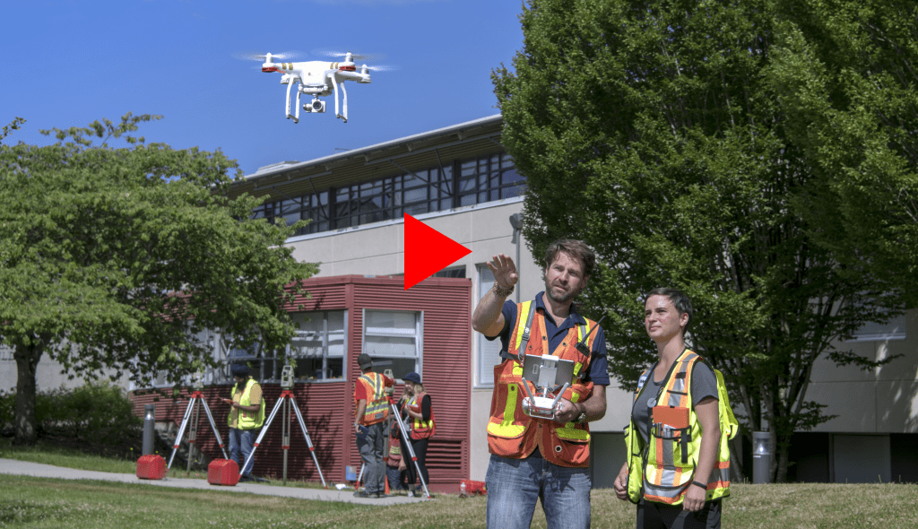 Instructor and student in safety vests watching drone