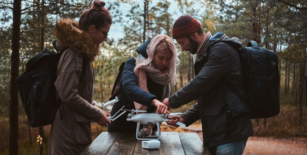 Three students in the woods with a drone on a picnic table